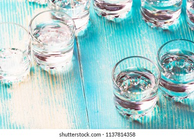 full glasses with alcohol on a blue table, the set is scattered chaotically