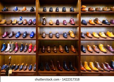 Full grain leather shoes on wooden display in men shoes boutique store. Black, brown and other colors.