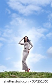 Full growth, beautiful young woman in sexy long gray dress