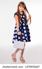 Full growth portrait of a beautiful little schoolgirl in polka dot dress and with white handbag