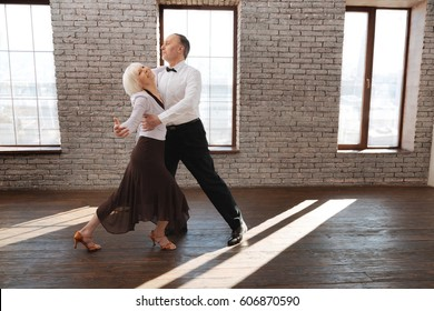 Full of harmony . Graceful talented flexible elderly couple dancing in the ballroom while improving dance skills and tangoing