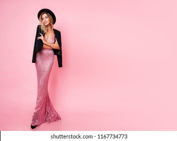 Full height  image of blonde woman with perfect wavy hairstyle  in pink sequin party dress posing on pastel pink background. Fashion boutique. Space for text.