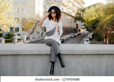 Full height image Playful black woman with Afro hairs sitting on the bridge and having fun. Wearing leather boots and whoop  trendy trousers . Travel mood. Happy leisure time in old European city.