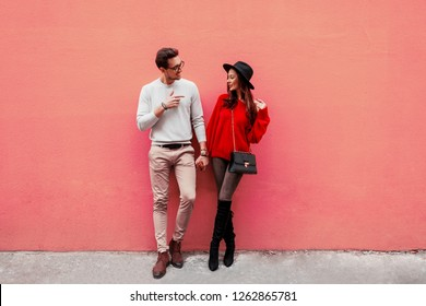 Full height image of playful couple in love posing over  pink wall. Traveling people. Brunette girl with handsome boyfriend traveling in Europe. Valentine's Day.