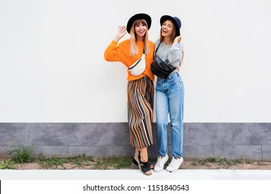 Full height image of two happy cheeky girls , best friends having fun , laughing on white  wall .  Outdoor. Autumn outfit