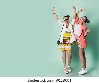 Full height image  of two happy cheeky girls  , best friends having fun , laughing on blue background. . Wearing stylish  casual jackets, striped pop dress. Space for text.