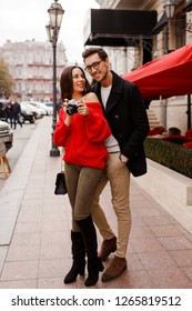 Full height outdoor image of fashionable elegant couple in love walking on the street during date or holidays.  Brunette woman in red sweater making photos by camera.