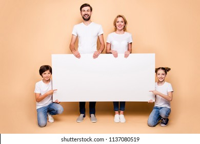 Full height portrait of adorable attractive family, bearded father, blonde mother holding copyspace with their little children wearing jeans and white T-shirts. Children pointing at copy-space