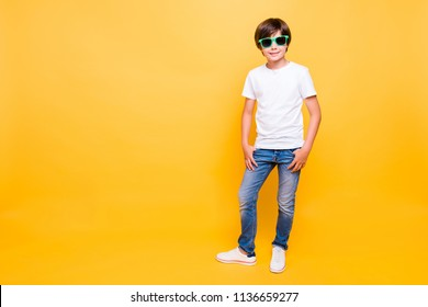 Full height portrait of attractive young cheerful school boy, smiling, wearing sun glasses standing over yellow background, isolated. Copy space