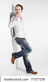 Full height portrait of young man leaning to a white wall