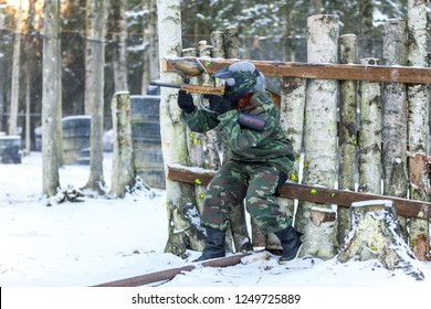 Full height portrait of young woman playing paintball outdoors in winter