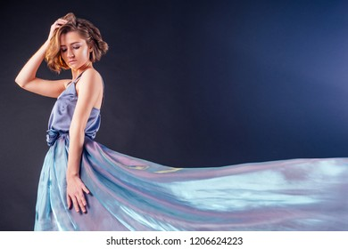 full height sensual and beautiful woman in gray blue waving sparkling dress posing with flying fluttering fabric in studio on black background.fashion photography model,perfect skin make-up hairstyle