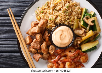 Full hibachi dish with rice, shrimp, steak and vegetables served with sauce closeup in a plate on a table. Horizontal top view from above