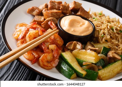 Full hibachi dish with rice, shrimp, steak and vegetables served with sauce closeup in a plate on a table. horizontal