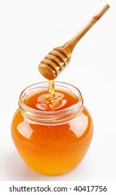 Full honey pot and honey stick isolated on a white background. Organic food.