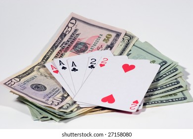 Full house of playing cards on top of United States fifty and twenty dollar bills on white back ground