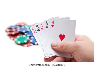 A full house poker hand, aces and kings with poker chips on white.