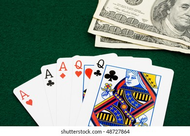 A full house sitting on a green background, playing poker
