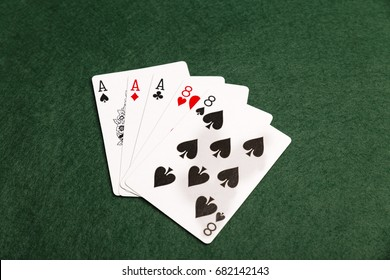 A full house of three aces and two eights on a green baize background