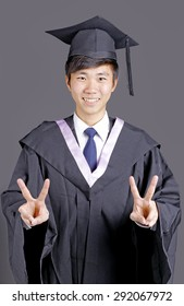 Full isolated studio picture from a young asian graduation man