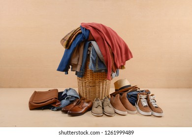 full of jeans, pile of clothes with different shoes, leather bag-- beige background
