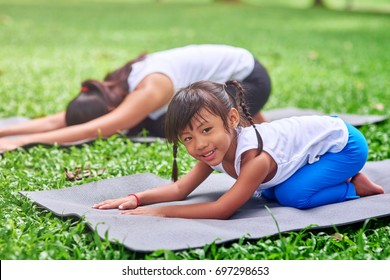 Full of joy. Positive cute little thai sitting on the roll mat and resting in the park while doing stretching exercises with her mother