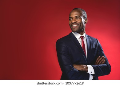 Full of joy. Waist-up portrait of cheerful cute young african businessman in suit is looking aside playfully while standing with crossed arms. Isolated background and copy space in the left side