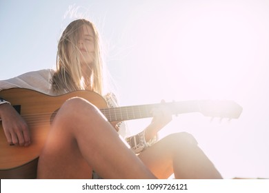 full of joyful feeling satisfaction for beautiful blonde young woman playing alone the acoustic guitar with the wind on his hair in summer time vacation leisure. pretty lady lifestyle.