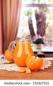 Full jug of tangerine juice, on wooden table on bright background