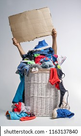 Full laundry white wicker basket on the grey background. Two hands hold a cardboard tablet