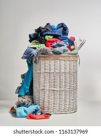 Full laundry white wicker basket on the grey background