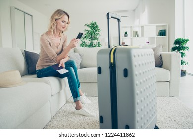 Full legs body size good-dressed nice-looking passenger lady with her calm profile side face she sit on comfort couch in modern light house book taxi texting sms message look at cellular screen