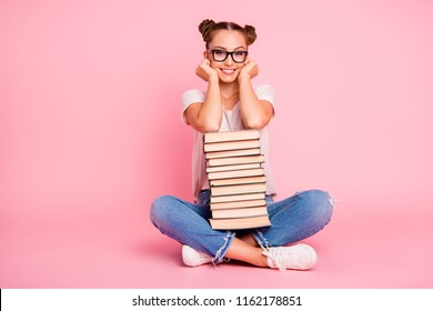 Full legs, body, size portrait of school reader girl in denim wear and white sneakers holds book, smile and looks at the camera isolated on shine pink background with copy space for text