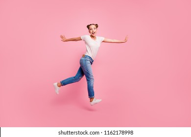 Full legs, body, size portrait of cute, lovely and sweet young brunette girl in white t-shirt and jeans jump against shine pink background