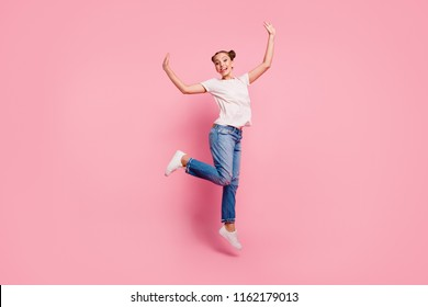 Full legs, body, size portrait of young cheerful funny girl in white t-shirt and blue jeans jumping up with hands to the sides biting her tongue isolated on bright pink background
