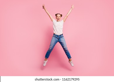 Full legs, body, size portrait of young brunette girl in white t-shirt and blue jeans jumping in the form of star closing her eyes and laughing loudly isolated on shine pink background