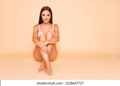 Full legs body size portrait of brunette hair lady she hug herself self sitting on the floor isolated on pastel beige background with her perfect ideal slim fit figure make beaming smile