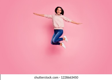 Full legs body size portrait of lady with her brunet hair hands aside she jump up wear in urban casual outfit isolated on bright pink background
