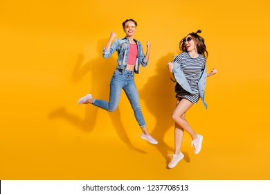 Full legs body size two dreamy charming lovely cute sweet lady in glasses spectacles cool trendy street style stylish casual denim jeans wear raised fists up isolated on yellow vivid background