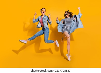 Full legs body size two attractive music lover leisure lifestyle cool lady isolated on yellow vivid background in glasses spectacles dance dancer on concert raised fists up give heavy metal gesture