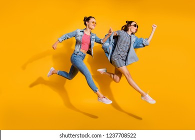 Full legs length body size portrait of two beautiful attractive glad positive grinning good-dressed lady in glasses spectacles isolated on yellow vivid background run away together