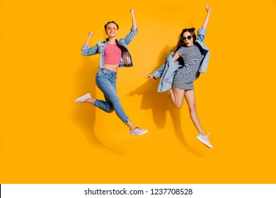 Full legs length body size portrait of two carefree careless dreamy charming lovely cute sweet lady in trendy casual wear glasses spectacles raised fists up isolated on yellow wall