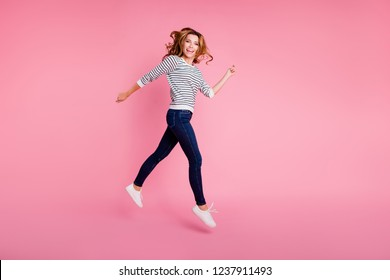 Full legs length body size profile side view beautiful attractive pretty dreamy charming lovely cute lady with her hairdo she look at camera isolated on pastel pink background in casual outfit