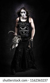 Full lendth portrait of man in goth style clothes with scull in his hand.