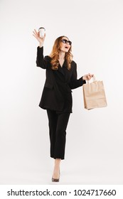 Full lengh portrait of a happy young businesswoman dressed in suit drinking coffee while holding shopping bags and waving hand isolated over white background