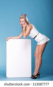 full lenght Beautiful young woman with pin-up make-up and hairstyle posing in studio with white board talk phone