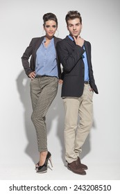 Full lenght picture of a young fashion couple posing on light grey background, both looking at the camera.