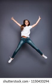 Full lenght portrait of brown-haired gorgeous attractive nice lovely excited smiling young lady wearing jeans and white t-shirt, raising hands up, flying jumping over grey background, isolated