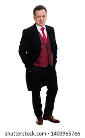 Full lenght Portrait of handsome confident caucasian mature businessman 55-60 years old in black tuxedo and red vest standing with hands in pockets smiling in front on isolated white background.