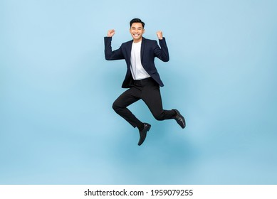 Full lenght portrait of smiling handsome Asian man jumping and raising  his fists on isolated light blue studio background